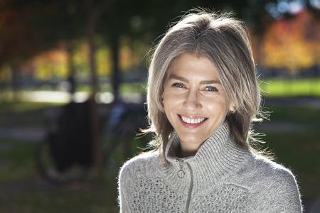 カメラに向かって笑みを浮かべて成熟した女性の肖像画。外。