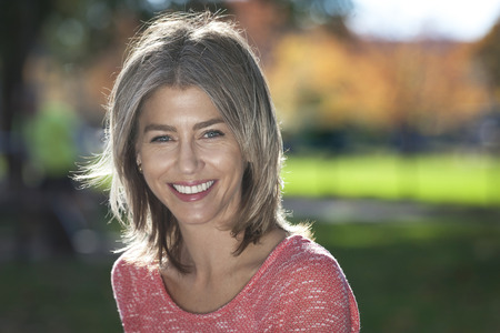 Portrait Of A Mature Woman Smiling At The Camera. Outside.