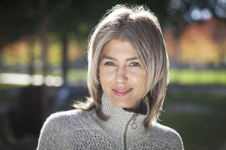 カメラに向かって笑みを浮かべて成熟した女性の肖像画。外。白髪が増える。