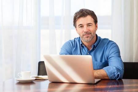 Porträt eines reifen Mannes, der ein kleines Lächeln auf einem Vorhängehintergrund hat Standard-Bild