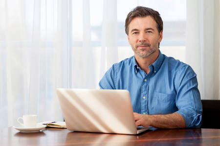 Mature man working at home in the kitchen