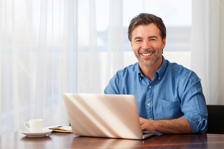 A portrait of a smiling middle-aged bearded man on a window background Stock Photo