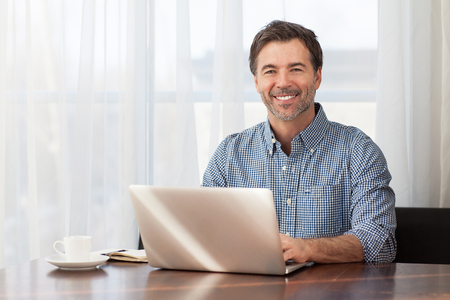 A portrait of a smiling middle-aged bearded man at a desk