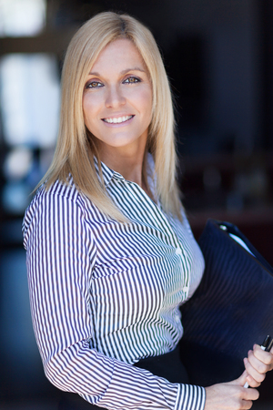 Blond mature businesswoman smiling at the camera. Office background. She is holding a document 写真素材