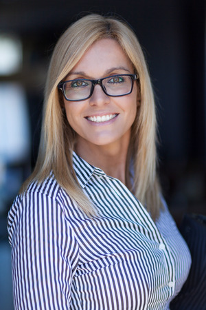 Pretty Mature Businesswoman smiling at the camera. She wears glasses Stok Fotoğraf