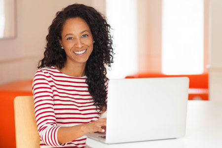 African American Woman Working on a laptop. She is really happy studying at home