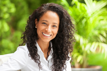 Portrait Of A African American Woman Sitting in the backyard of her house. She is really happy. Standard-Bild