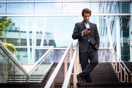 Portrait Of A Successful Businessman On The Phone. In front of building