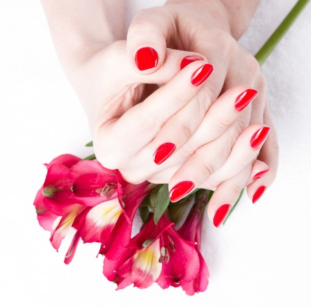 Closeup image of red manicure with flowers photo