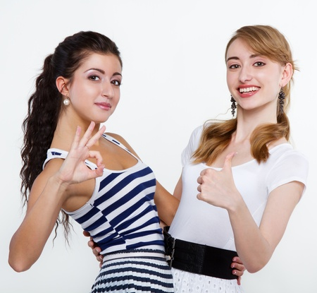 Portrait of happy young friends showing thumbs up sign Stock Photo - 15555371