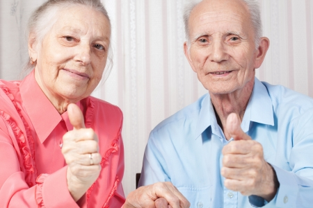 Closeup portrait positive elderly couple happy, thumbs-up gesture photo