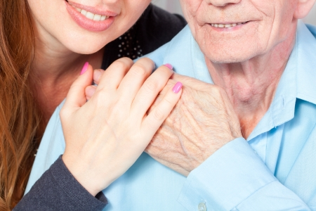Senior man with her caregiver at home Stock Photo