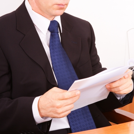 Businessman reading a letter. Close-up on a white background. photo