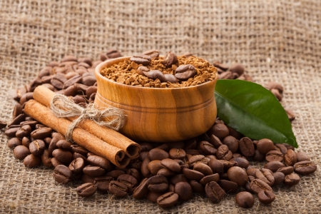 coffee beans in a wooden bowl on burlap background photo