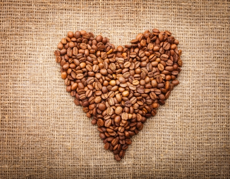 Heart from coffee beans  on textured brown sack Stock Photo