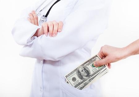 Patient bribing doctor, putting money to pocket Stock Photo - 17664841