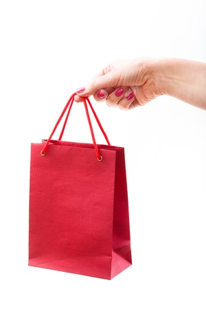 Red paper bag in female hand photo