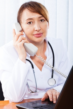 Woman doctor consults by phone Stock Photo - 17890307