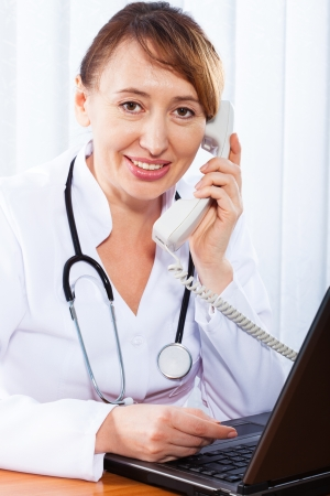 Woman doctor consults by phone photo