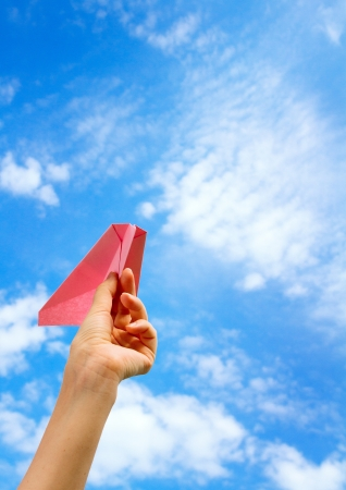 woman starts paper plane in blue sky  photo