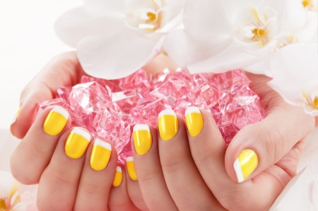 Woman in nail salon receiving manicure by beautician photo