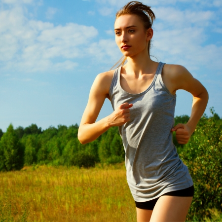 Portrait of a young woman jogging in nature  Close up photo