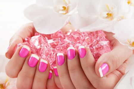manicure and pedicure: Woman in nail salon receiving manicure by beautician Stock Photo