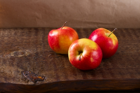red apples on a wooden table still life close up photo