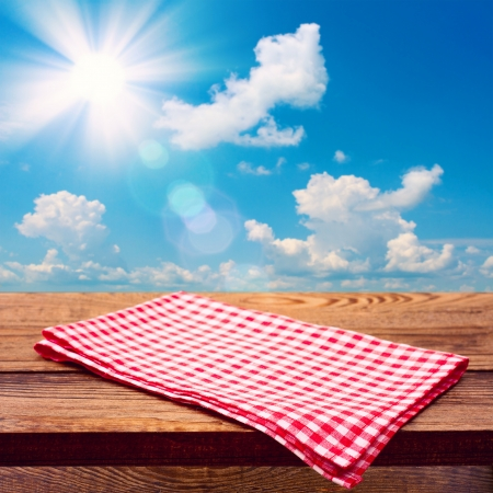 Empty wooden deck table with tablecloth for product montage. Free space for your text photo