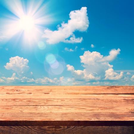 Leere Holzdeck Tisch mit Tischdecke für die Produktmontage. Sunny Day, blauer Himmel mit Wolken Freier Platz für Ihren Text