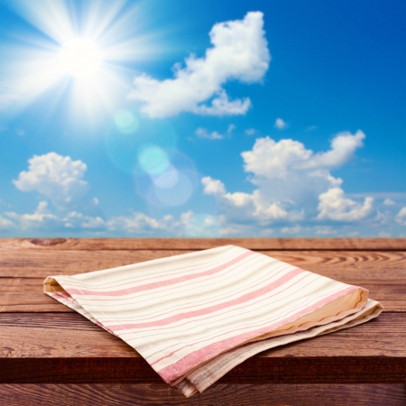Empty wooden deck table with tablecloth for product montage. Sunny Day, Blue Sky with Clouds Free space for your text