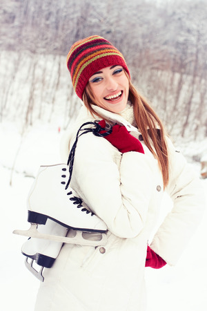 iceskates: Beautiful young woman smiling happily. Winter activities at the rink with skates Stock Photo