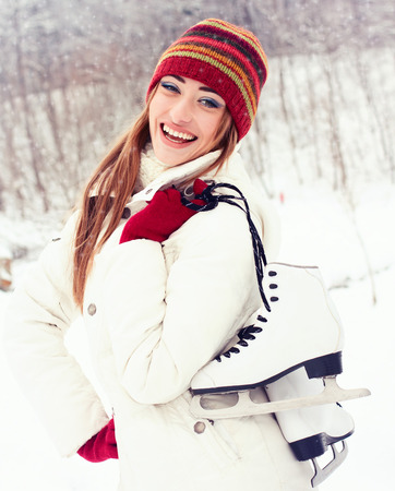 Beautiful young woman smiling happily  Winter activities at the rink with skates photo