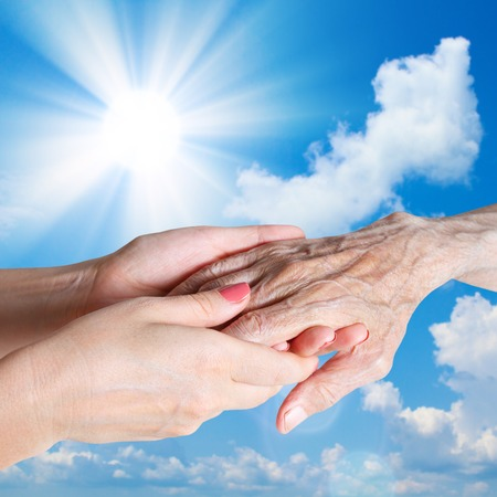 Hands Senior Man, Woman with their Caregiver summer on sunny blue sky background  Concept of Health Care for Elderly Old People, Disabled photo