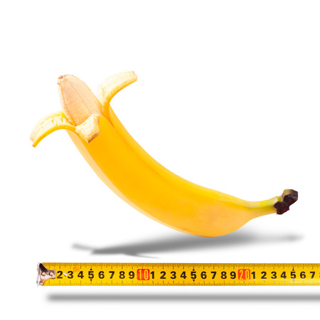 Large banana and measuring tape as image of mans penis Reklamní fotografie