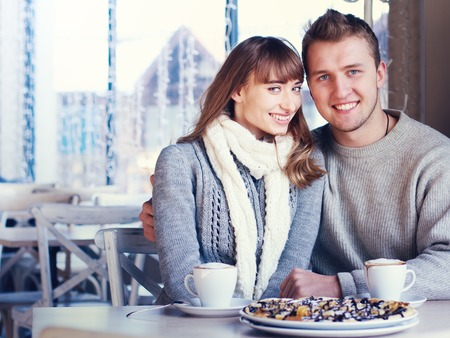 Portrait of Beautiful Young Couple in Love, couple having fun talking in cafe and drink coffee. Concept of relationship, love story, preparations for wedding, fashionable clothing photo