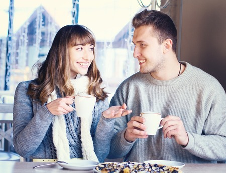 Portrait of Beautiful Young Couple in Love, couple having fun talking in cafe and drink coffee. Concept of relationship, love story, preparations for wedding. photo