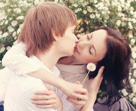 young couple kissing: Portrait of Beautiful Young Couple in Love on nature. Man and Woman Smiling Charmingly. Young Couple Kissing Summer on Sunny Sky Background Stock Photo