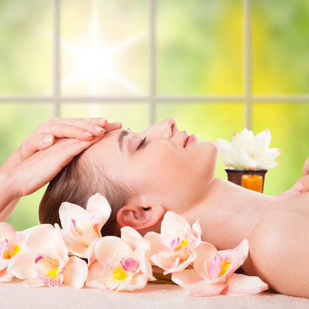 Beautiful Young Woman Getting Massage Facial and Body in Spa Salon  Treatment Cosmetics Beauty Care Body Herbs Surrounded by Flowers photo