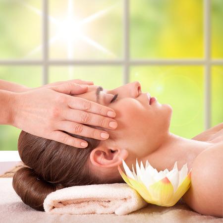 Schöne junge Frau bekommen Massage Gesichts-und Körperbehandlung im Spa Salon Kosmetik Beauty Pflege Körper Kräuter, umgeben von Blumen