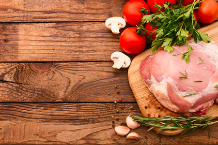Sliced pieces of raw Meat for barbecue with fresh Vegetables and Mushrooms on wooden surface. Meat Raw Steak. Beef Steak BBQ. Tomatoes, peppers, spices for cooking meat. Stock Photo - 26656628