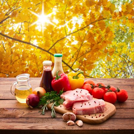 Food. Raw meat for barbecue with fresh vegetables and mushrooms on wooden surface. Tomatoes, peppers, spices for cooking meat. Autumn landscape. Collage.