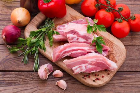Sliced ​​pieces of raw Meat for barbecue with fresh Vegetables and Mushrooms on wooden surface. Meat Raw Steak. Beef Steak BBQ. Tomatoes, peppers, spices for cooking meat. photo
