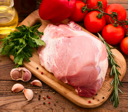 Food. Sliced ​​pieces of raw meat for barbecue with fresh vegetables and mushrooms on wooden surface. Meat raw steak. Beef steak bbq. Tomatoes, peppers, spices for cooking meat. photo