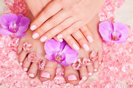 Manicure and pedicure, beautiful orchid flowers closeup photo