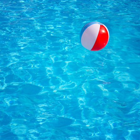 furlough: Inflatable colorful ball floating in swimming pool Stock Photo