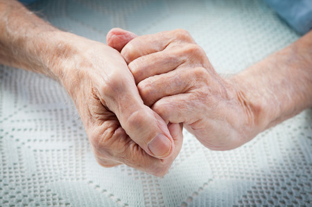 Care is at home of elderly. Old people holding hands. Closeup. photo