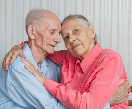 Closeup portrait of smiling elderly couple. Old people holding hands. Concept of marital fidelity, providing for old age, reliability photo