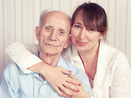 Senior man, woman with their caregiver at home. Concept of health care for elderly old people, disabled Stock Photo