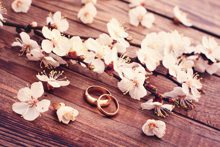 Wedding rings. Flowering branch with white delicate flowers on wooden surface. Declaration of love two hearts couple space for text photo